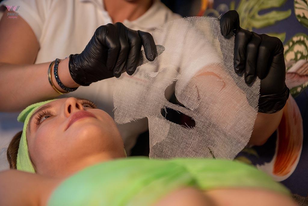 kosmetyczka trzyma w ręku płachtę maseczki nad leżącą klientką