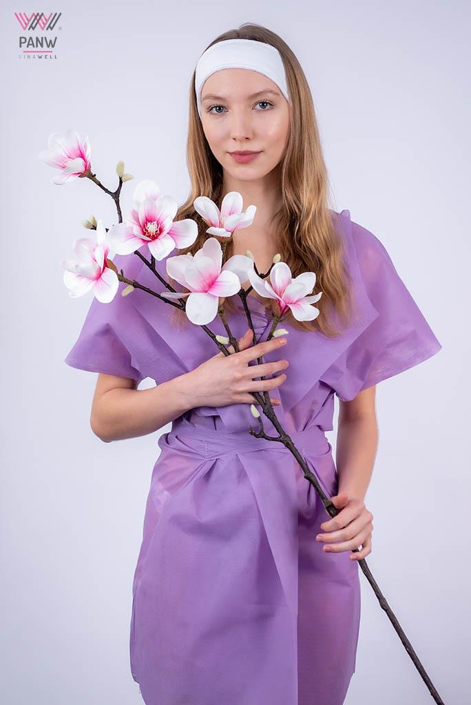 młoda blondynka w fioletowym szlafroku i białej opasce trzyma w ręku gałązkę z kwiatami