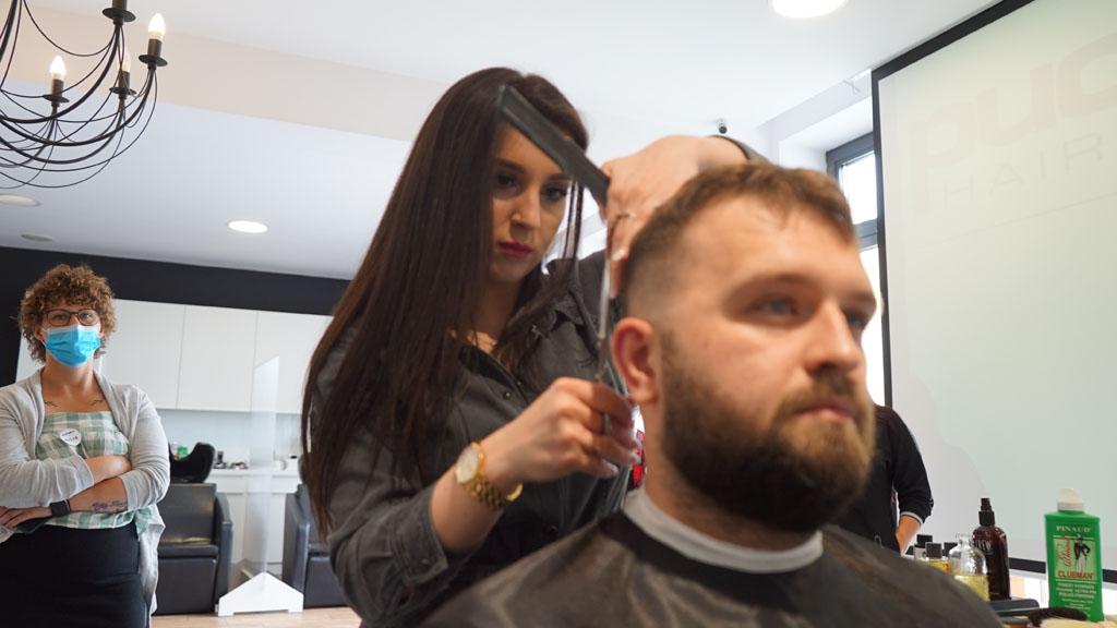 fryzjerka strzyże włosy mężczyzny na szkoleniu