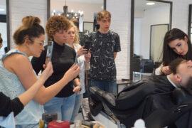 fryzjerka strzyże brodę mężczyzny podczas szkolenia