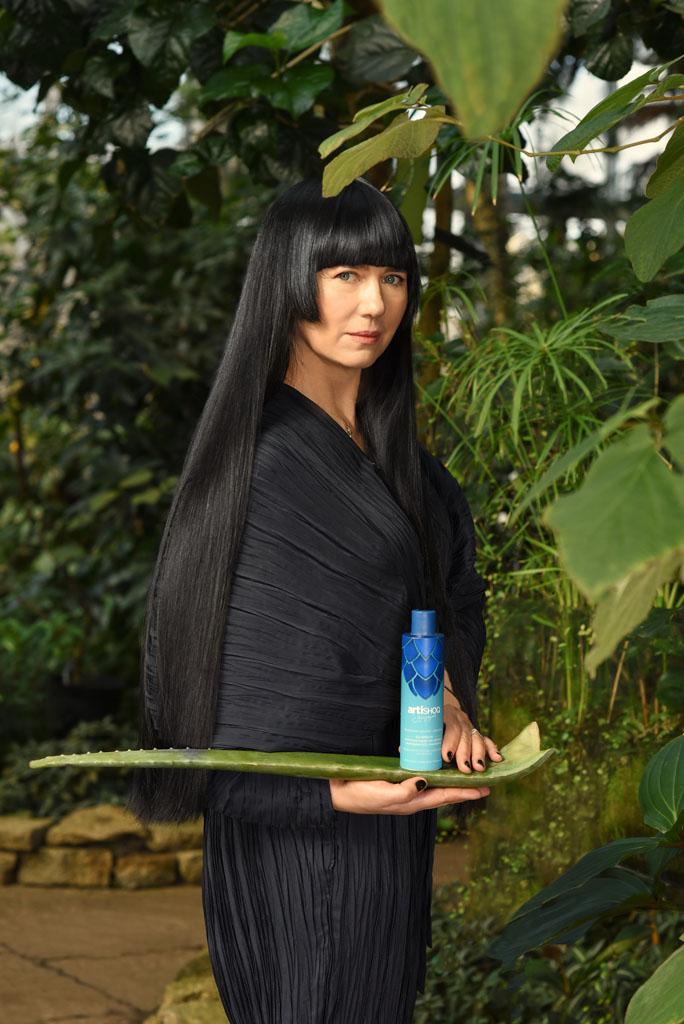 kobieta z długimi czarnymi włosami trzyma kosmetyk na liściu