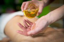 masażystka wylewa olejek do masażu na dłoń