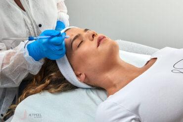 kobieta leżąca z opaską na włosach podczas zabiegu złuszczania w salonie kosmetycznym