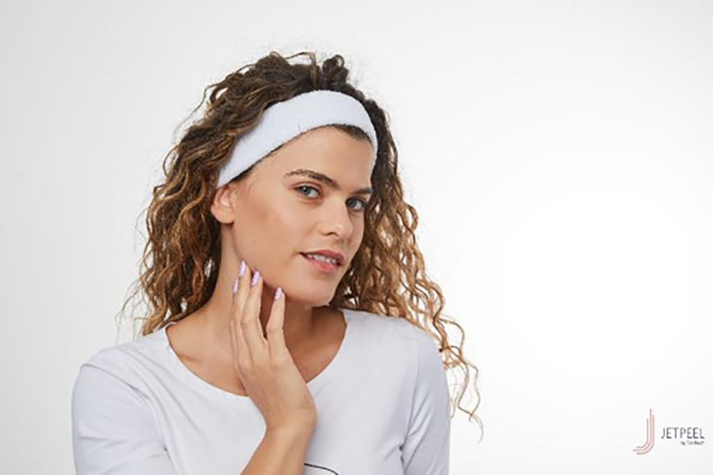 kobieta po zabiegu z opaską na włosach dotykająca swojej twarzy