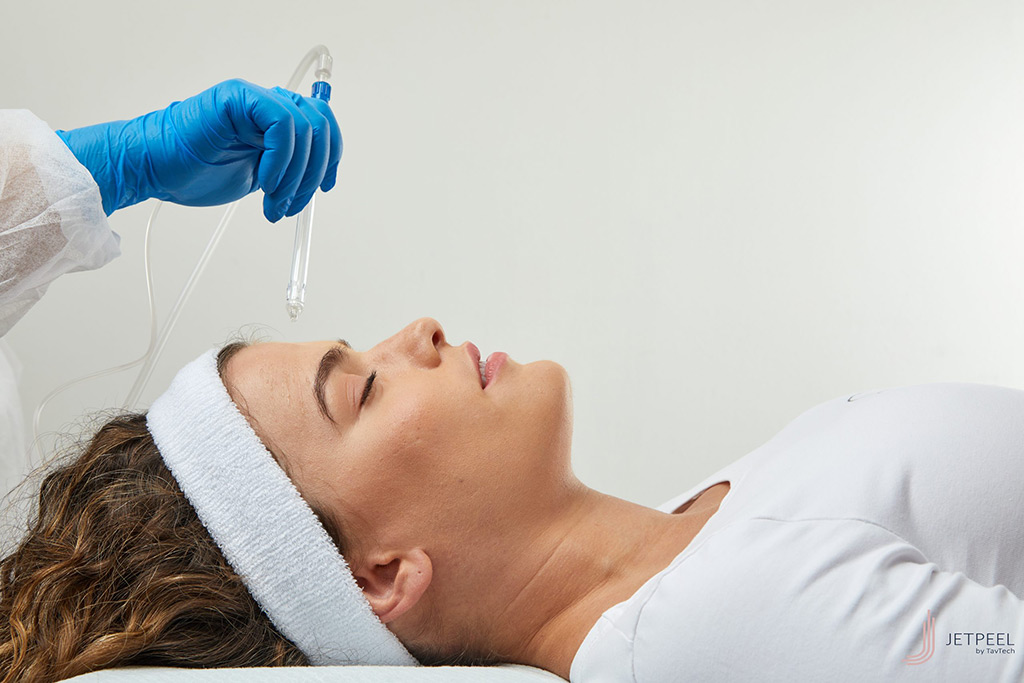 leżąca kobieta z opaską na włosach podczas zabiegu kosmetycznego
