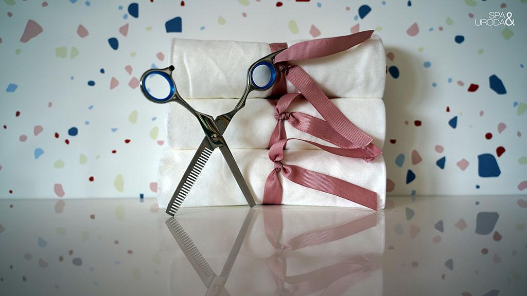 nożyczki z ręcznikami ułożonymi w stosik w tle