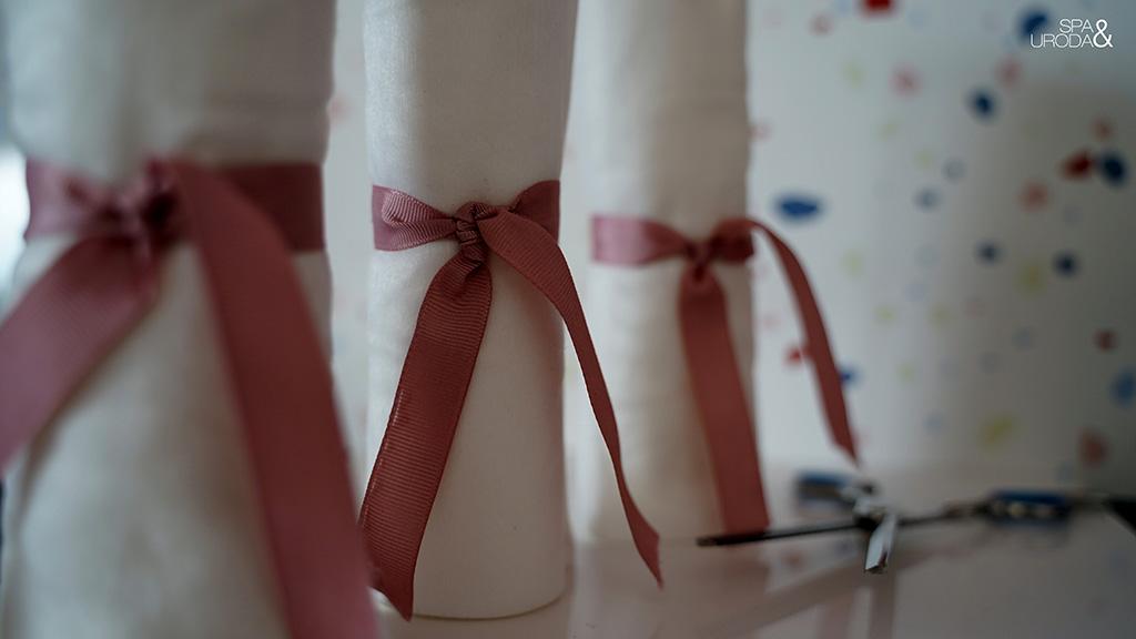 ręczniki zwinięte w rulony ustawione jak kolumny i przewiązane wstążeczkami