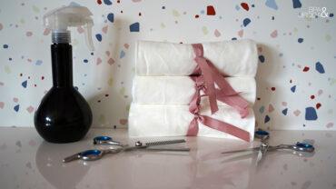 stosik z ręczników jednorazowym przewiązanych różową tasiemką obok narzędzi fryzjerskich
