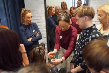 uważnie słuchający kursanci podczas szkolenia fryzjerskiego