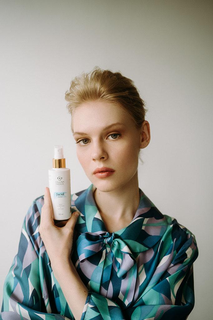 kobieta pozuje z kosmetykiem przy twarzy