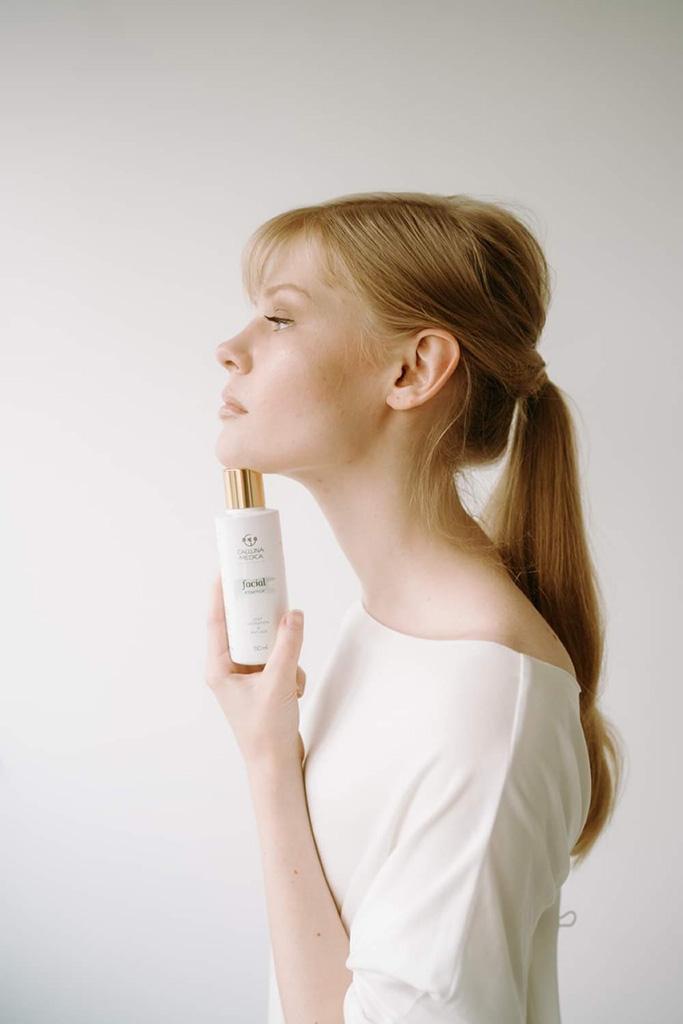 kobieta z profilu trzymająca kosmetyk pod brodą