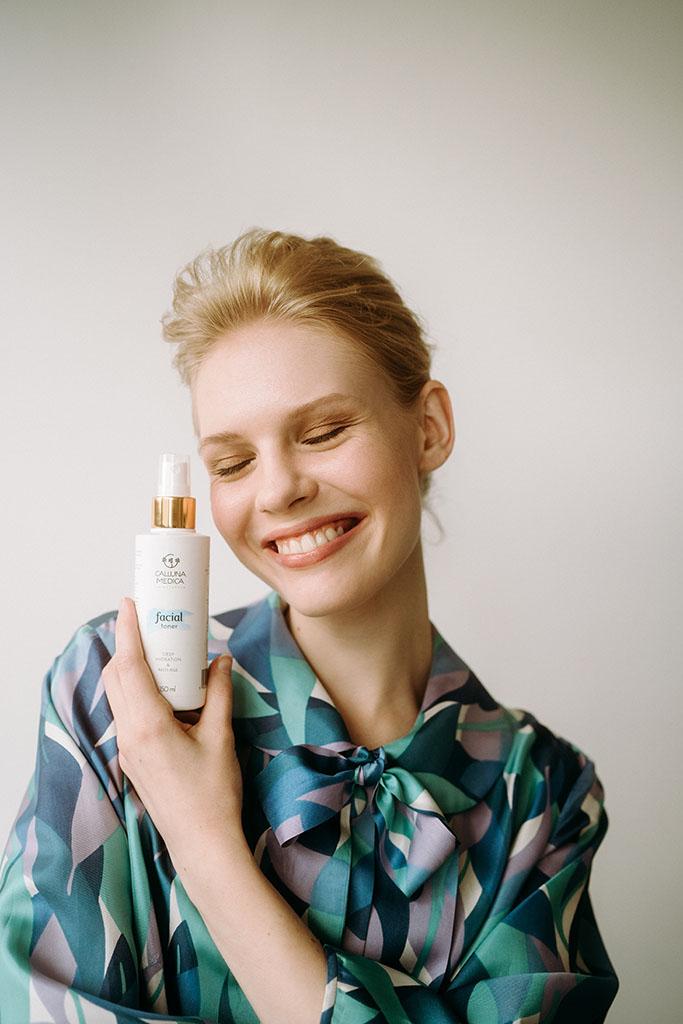 młoda blondynka uśmiecha się trzymając kosmetyk przy twarzy