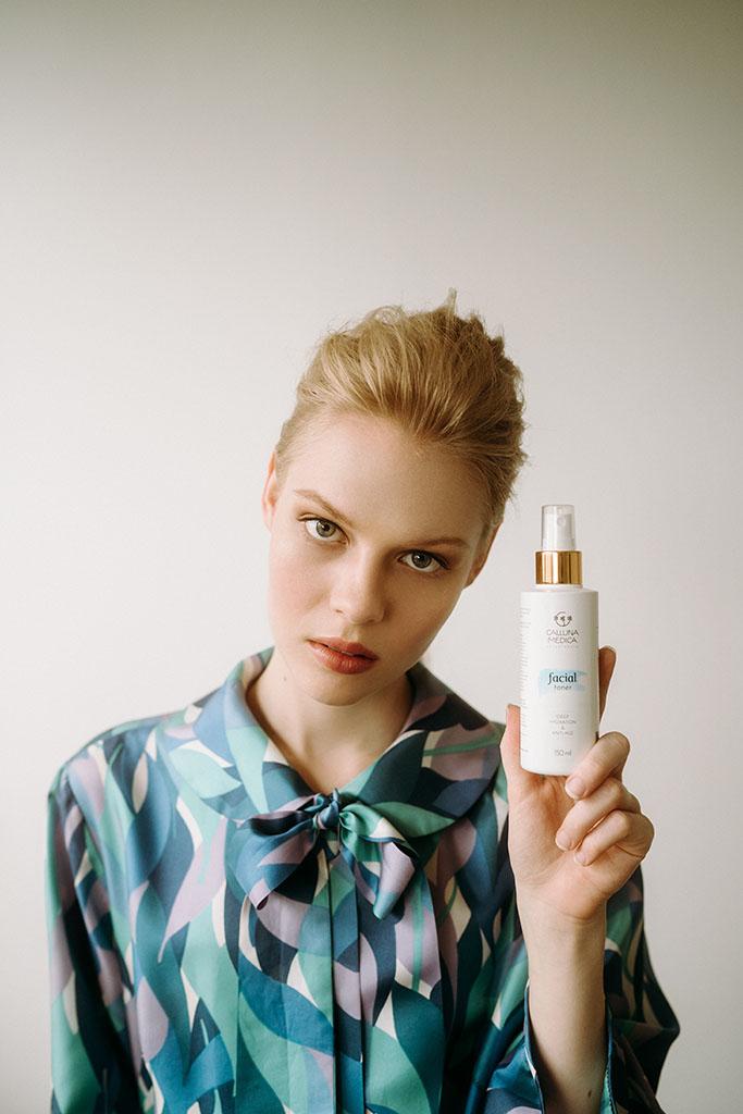 młoda kobieta trzyma kosmetyk w dłoni