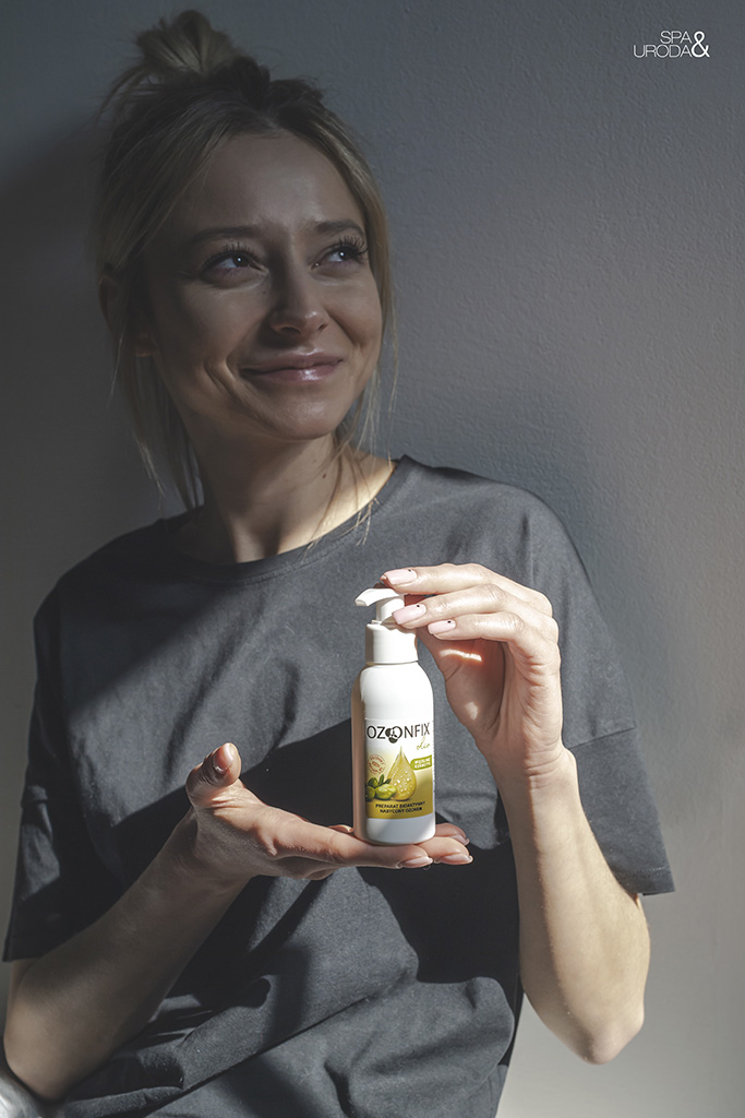 młoda kobieta trzyma w dłoniach butelkę kosmetyku