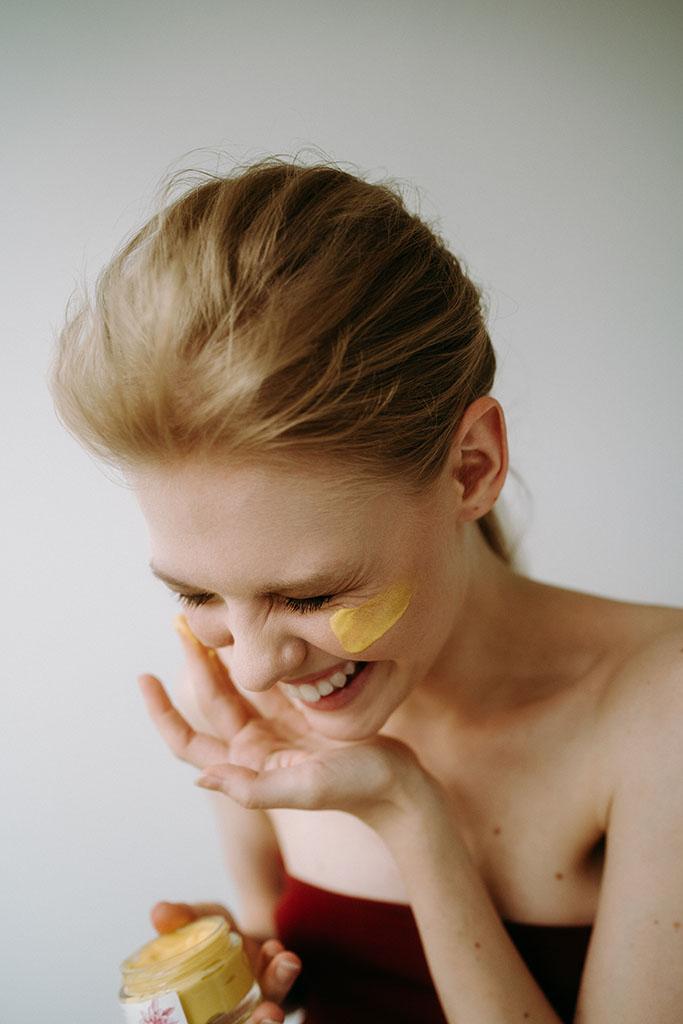 roześmiana kobieta nakłada krem na twarz