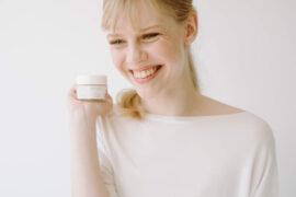 uśmiechnięta młoda kobieta trzyma słoiczek z kosmetykiem na dłoni