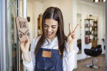 szczęśliwa kobieta obracająca tabliczkę o otwarciu gabinetu kosmetycznego