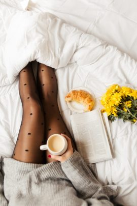 Woman sitting in bed reading newspaper and having breakfast. Top view