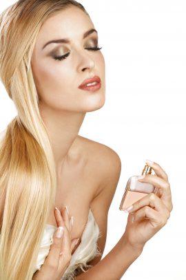 elegant woman applying perfume on her body on white